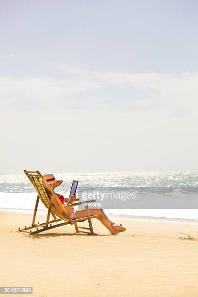 Vacances d'été à la plage en lisant avec tablette ordinateur portable verticale
