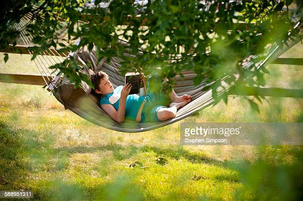 summer, boy reading in a hammock