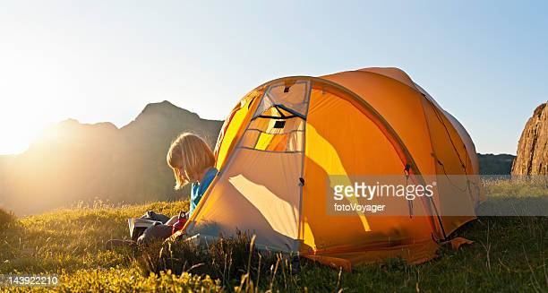 Summer camp child reading by mountain tent