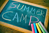 text summer camp written with chalk on a chalkboard, and some chalk sticks of different colors