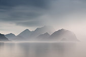 Summer cloudy Lofoten islands. Norway misty sea and fjords. Nordic rain.
