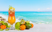Summer cocktail with various tropical fruits around. Apple, kiwi, tangerine, orange, mango, carambola. Glass of orange drink with blur beach on background
