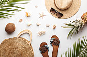 Summer composition. Fruits, hat, tropical palm leaves, seashells on white background. Summer concept. Flat lay, top view, copy space.