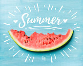 Summer concept. Slice of watermelon on turquoise blue background, top view. White lettering inscription