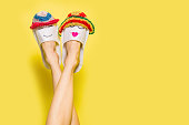 Summer couple in love concept. Female legs wearing hotel slippers with sumer hats over bright yellow background
