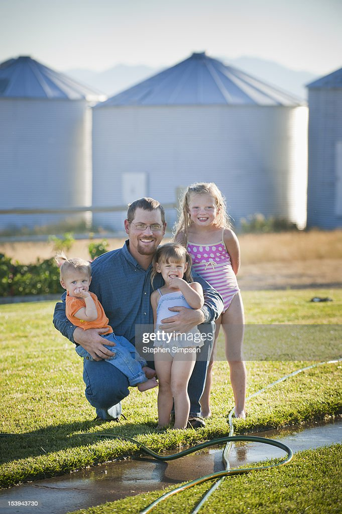 Summer evening, farmer and his daughters : Stock Photo