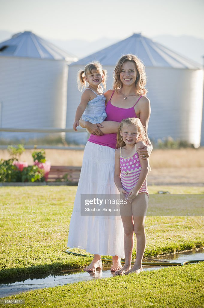 Summer evening, rural mom and her girls : Stock Photo