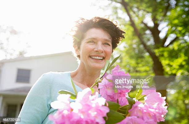 A summer family gathering at a farm. A woman carrying a large bunch of rhododendron flowers, smiling broadly.