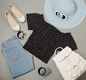Summer fashion set of blue hat, jeans, polka-dot top, shoes and backpack, sunglasses and bracelets. Selective focus.