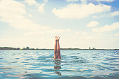 Woman's legs above the water. Unrecognizable woman diving in the sea. Copy space.