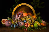 Assorted summer fruit displayed on a tabletop in front of a large brass bowl against a dark background.