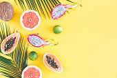 Summer fruits. Tropical palm leaves, pineapple, coconut, papaya, dragon fruit, orange on yellow background. Flat lay, top view, copy space