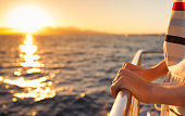 Closeup of female hands on a yacht during sunset.