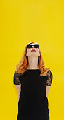 Pinnable vertical banner with woman in retro sunglasses and red lipstick on yellow background looking up. Beautiful woman with copyspace.