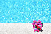 Red flip flops and sunglasses beside swimming pool