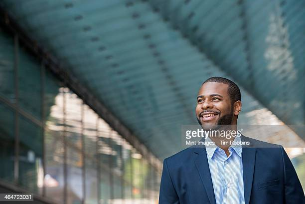 Summer in the city. Businesspeople outdoors, on the go. A man in a blue jacket and open necked shirt.