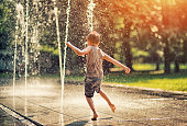 Summer in the city - little boy playing with fountain