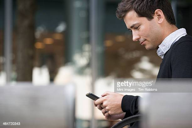 Summer in the city. People outdoors, keeping in touch while on the move. A man sitting on a bench using a smart phone.