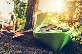 Summer Kayaking Time. Green Modern Kayak on the River Shore. Closeup Photo. Outdoor Recreation and Sport Theme.