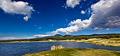 A wide angle high dynamic range image of a lake with mountains and blue sky in the background shot in Colorado.