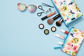 Beach holiday, make-up, flat lay, blue background, beauty product, sunglasses,