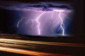 A summer monsoon thunderstorm with cloudtoground lightning strikes and car and truck light trails in the foreground Westcentral New Mexico USA...