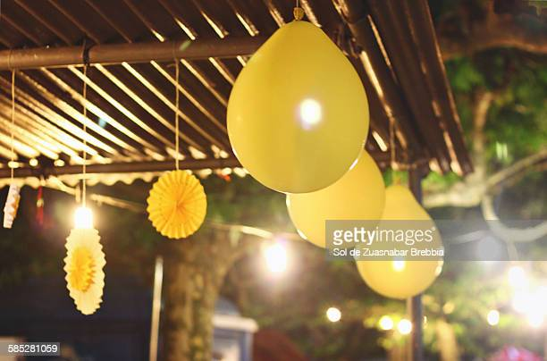 Summer nights. Yellow balloons hanging in the nigh