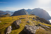 Beautiful Vibrant Norwegian Mountain Landscape from Ryten peak - famous mountain in Lofoten Islands, Moskenes municipality, Nordland with a view of Kvalvika beach, with hiking tourists and blue sky