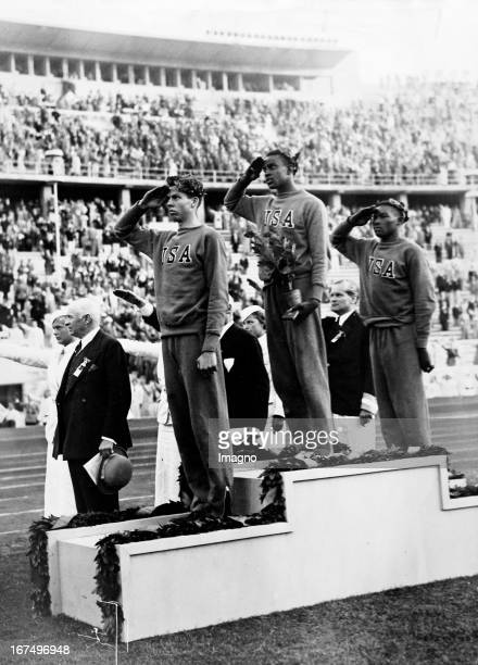 Summer Olympics Berlin 1936 The medal ceremony for high jump On the podium the three American atheltes Cornelius Johnson David Albritton and Delos...