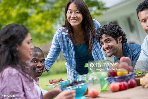 A summer party outdoors. Four people at a table.