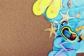 Beach accessories on wooden background. Flip flops, scuba mask, sea stars, towel