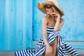 Woman portrait on blue background, sitting on the steps in a nice big straw hat and sun glasses, red lipstick and beautiful white teeth, with long blonde hair in a long striped dress with bare shoulde