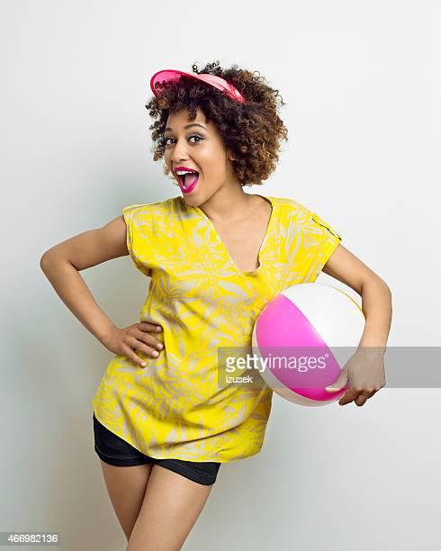 Summer portrait of afro girl holding beachball
