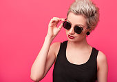 Colorful summer portrait of an attractive young woman with sunglasses over pink color background. Short hairstyle and bright make up