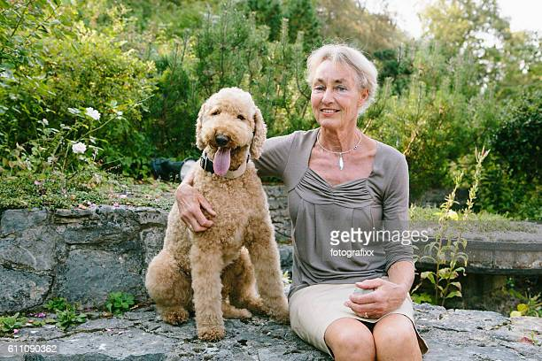 summer portrait: senior woman with her dog (labradoodle), arms around