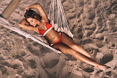Full length top view of attractive young woman in swimwear keeping hands behind head while lying down in hammock outdoors