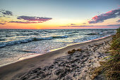 Sunset on the coast of Lake Michigan with a sandy beach in the foreground and a sunset horizon as the backdrop. Shot in horizontal orientation with copy space.