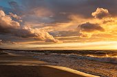 Cloudy sunsets with sun and reflections at the Baltic bay, Latvia