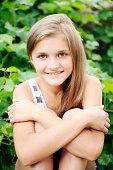 [b]Summer[/b], [b]Spring[/b], [b]Preadolescent[/b] girl, blonde hair, smiling having fun sitting on the grass, bushes behind her.