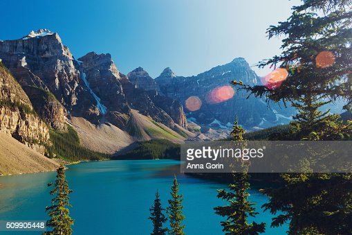 Summer sunset at Moraine Lake, Canada, surrounded by snowcapped peaks, lens flare and vintage tint