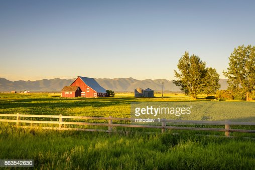 Summer sunset with a red barn in rural Montana and Rocky Mountains : Stock Photo