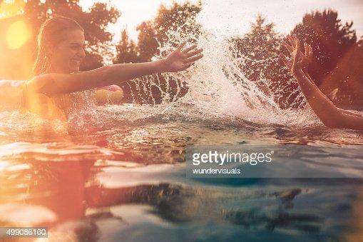 Summer swimming pool with girls splashing water playfully
