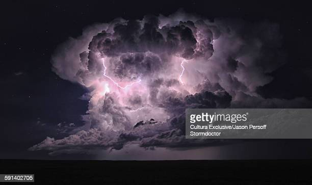 A summer thunderstorm erupts in a clear night sky near midnight over the Colorado Plains, Walsenberg, Colorado, USA
