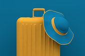 Minimal Summer travel concept, hat and suitcase on blue pastel background.