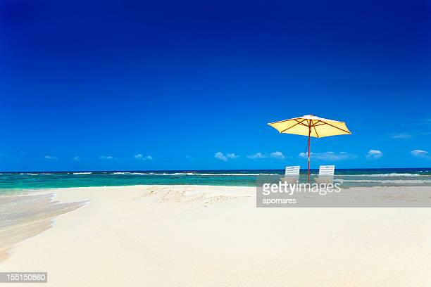 Summer tropical white sand beach with umbrella and chairs