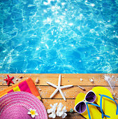 Vacation Concept - Beach Accessories On Table On Swimming Pool