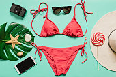 Red, pink bikini suit, lollipop, sunglasses, smartphone, film camera, hat on plain light cyan background. Empty space for copy, text, lettering. Summer vacation concept.
