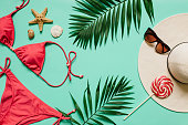 Red, pink bikini suit, lollipop, sunglasses, sea star on plain light cyan background. Empty space for copy, text, lettering. Summer vacation concept.