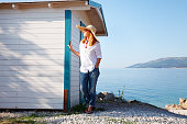 Full length portrait of middle age woman standing by the beach house. Beautiful female wearing casual clothes and straw hat during on her summer vacation.