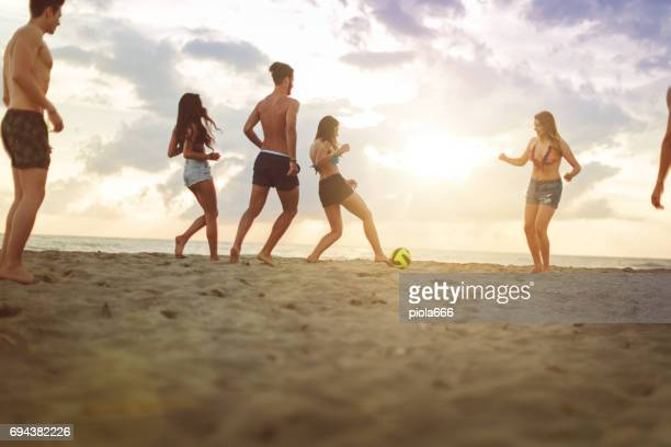 Summer vacation with friends: playing soccer on the beach
